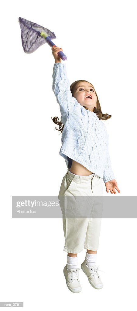 silhouette of a caucasian female child with a butterfly net as she playfully jumps up : Stockfoto