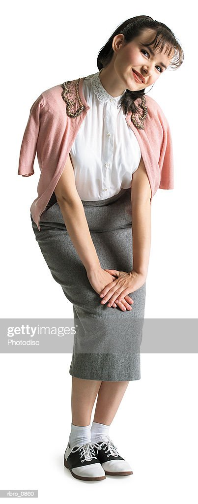silhouette of a caucasian female teen dressed in 1950's retro clothing as she smiles at the camera : Stockfoto