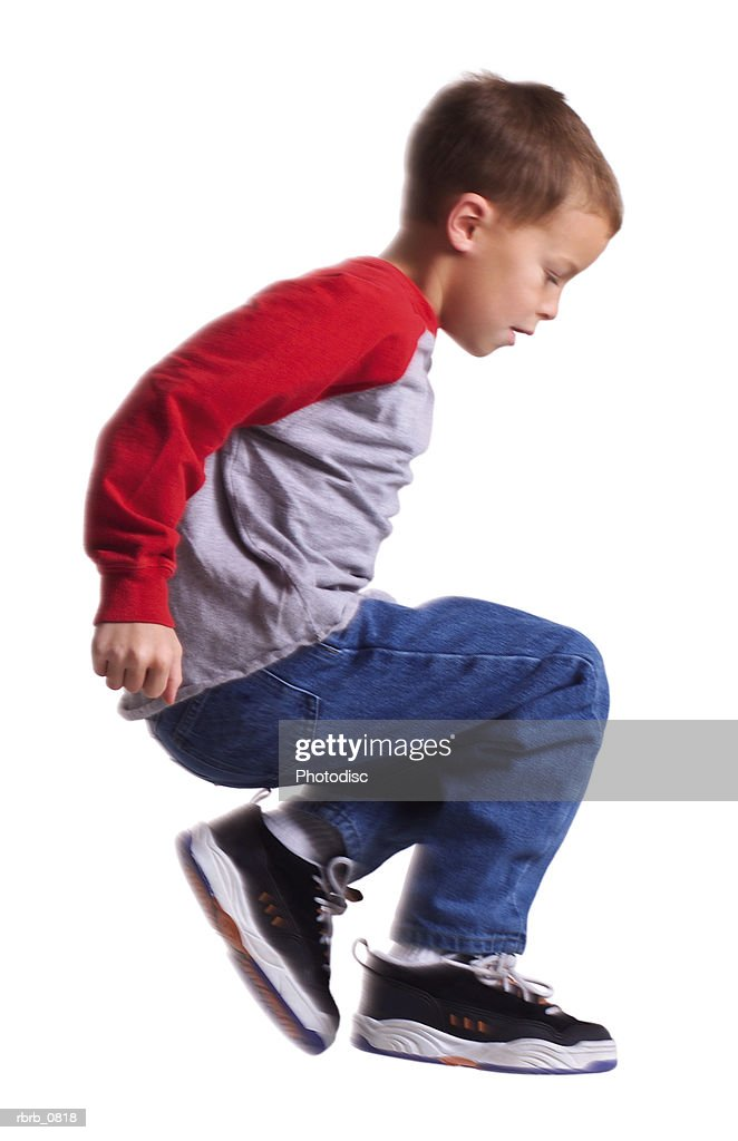 silhouette of a caucasian male child in jeans and a red shirt as he jumps sideways through the air : Stockfoto