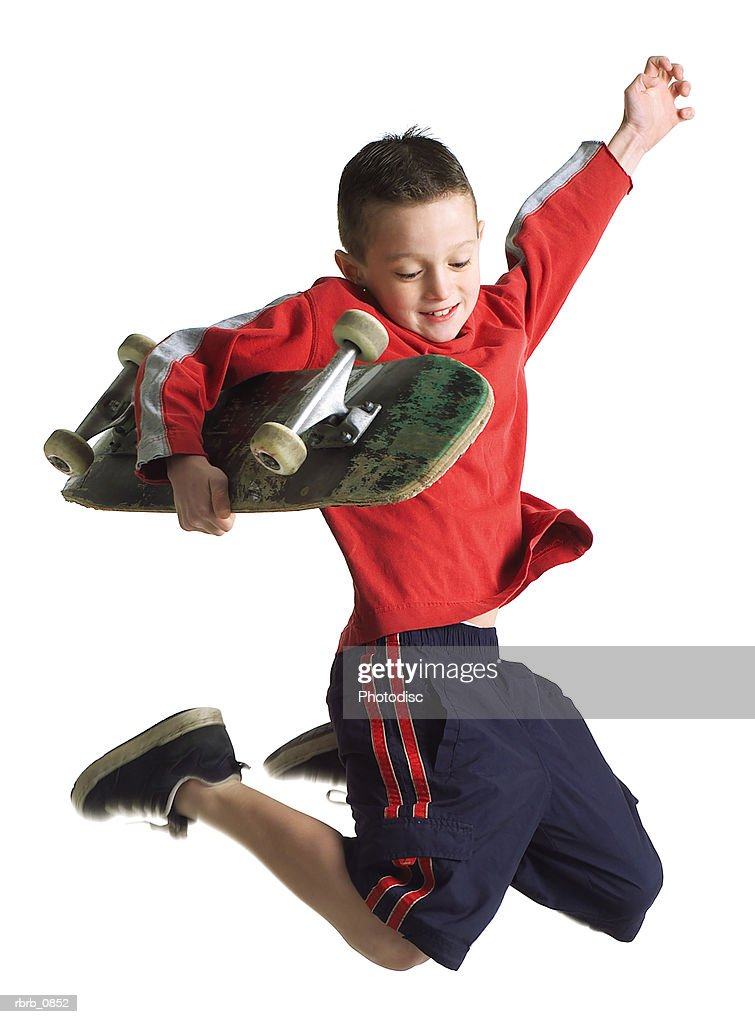silhouette of a caucasian male teenager as he jumps up holding his skateboard : Stockfoto
