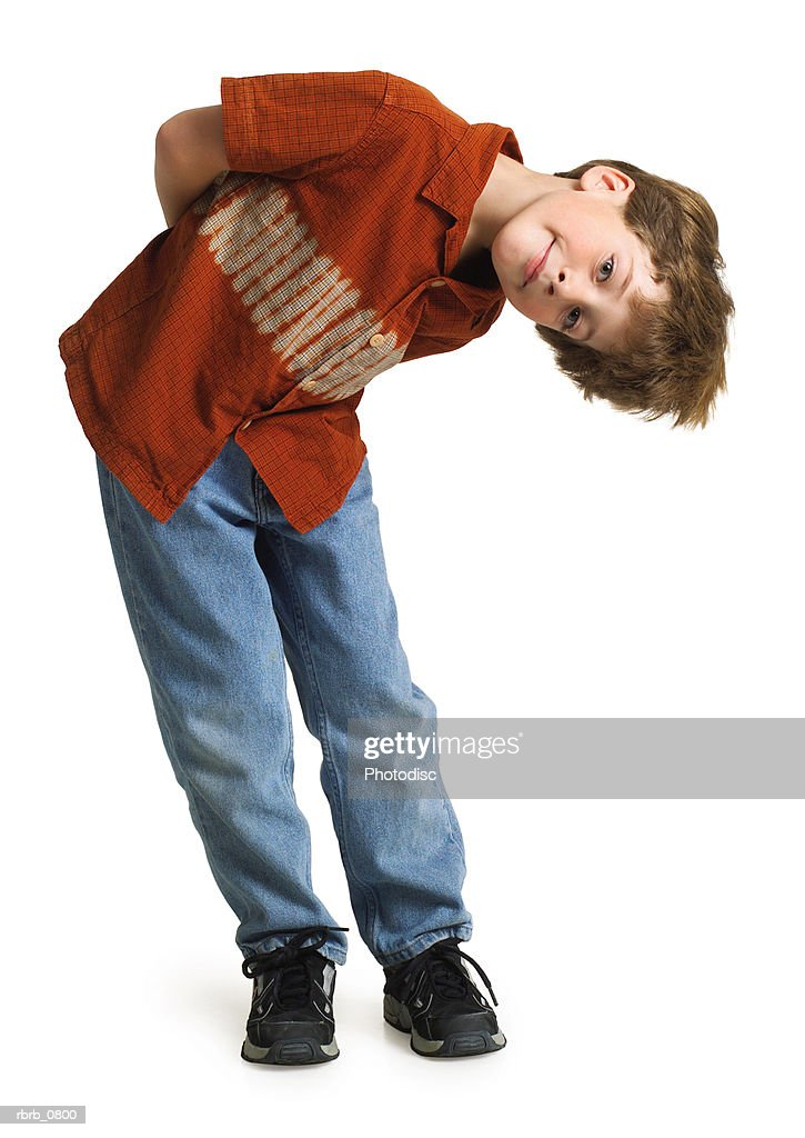 silhouette of a caucasian redheaded male child in jeans and a red shirt playfully bends to the side : Stockfoto