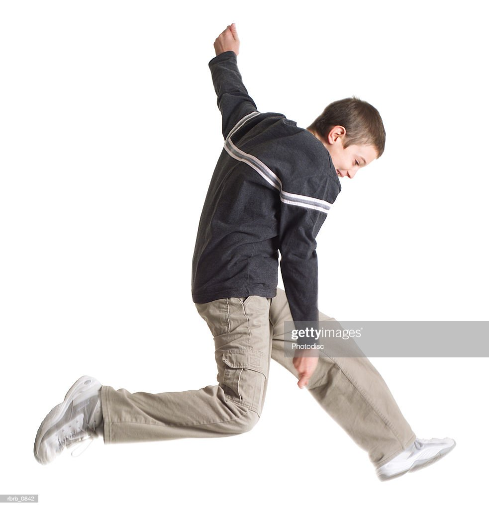 silhouette of a caucasian teenage boy in tan pants and a blue shirt as he wildly jumps through the air : Stockfoto