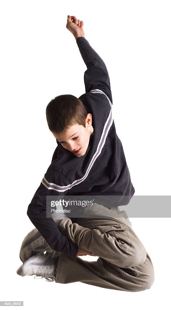 silhouette of a caucasian teenage boy in tan pants and a blue shirt as he jumps up and grabs his feet : Stock Photo