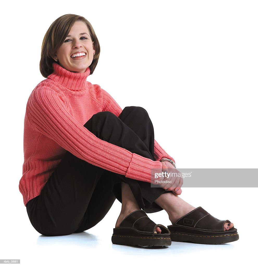 silhouette of a caucasian teenage female in black pants and a pink shirt as she sits and smiles : Stockfoto