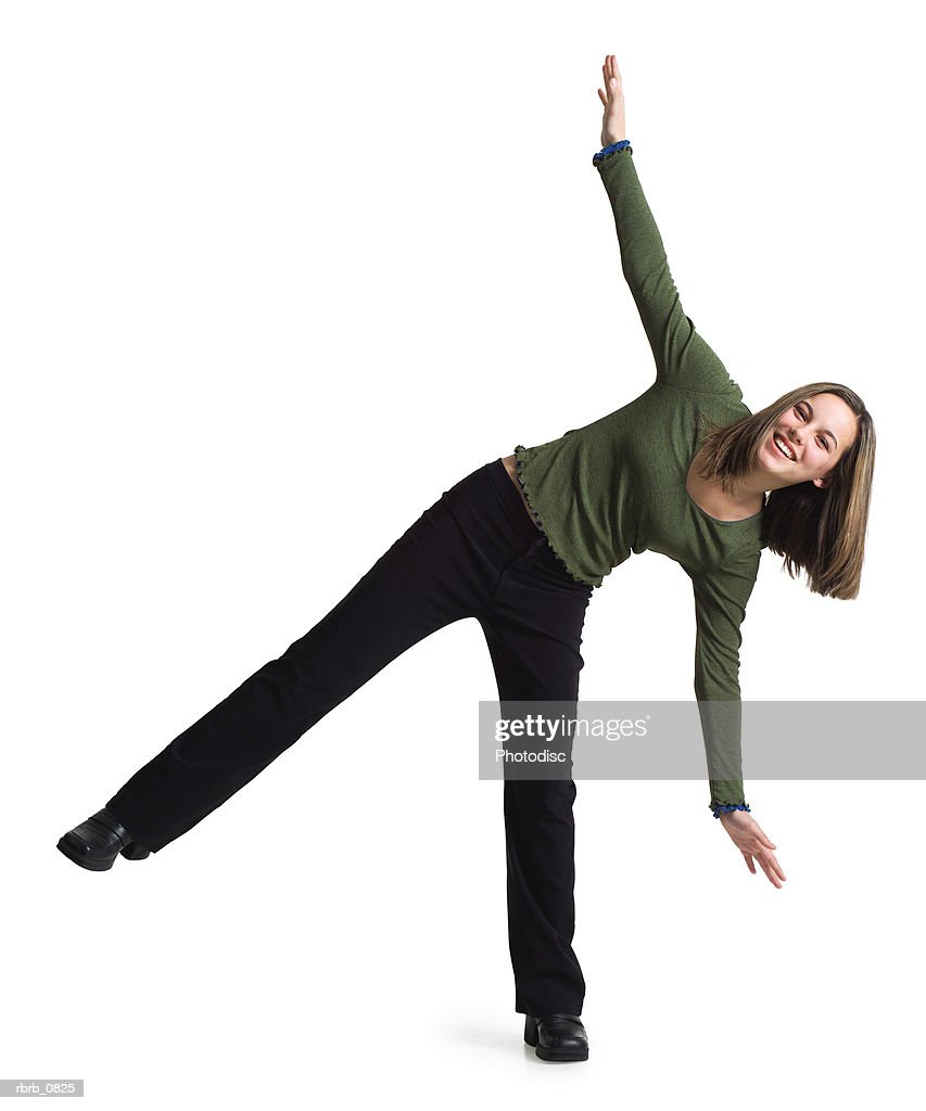 silhouette of a caucasian teenage girl in black pants and a green shirt as she balances on one leg : Stockfoto