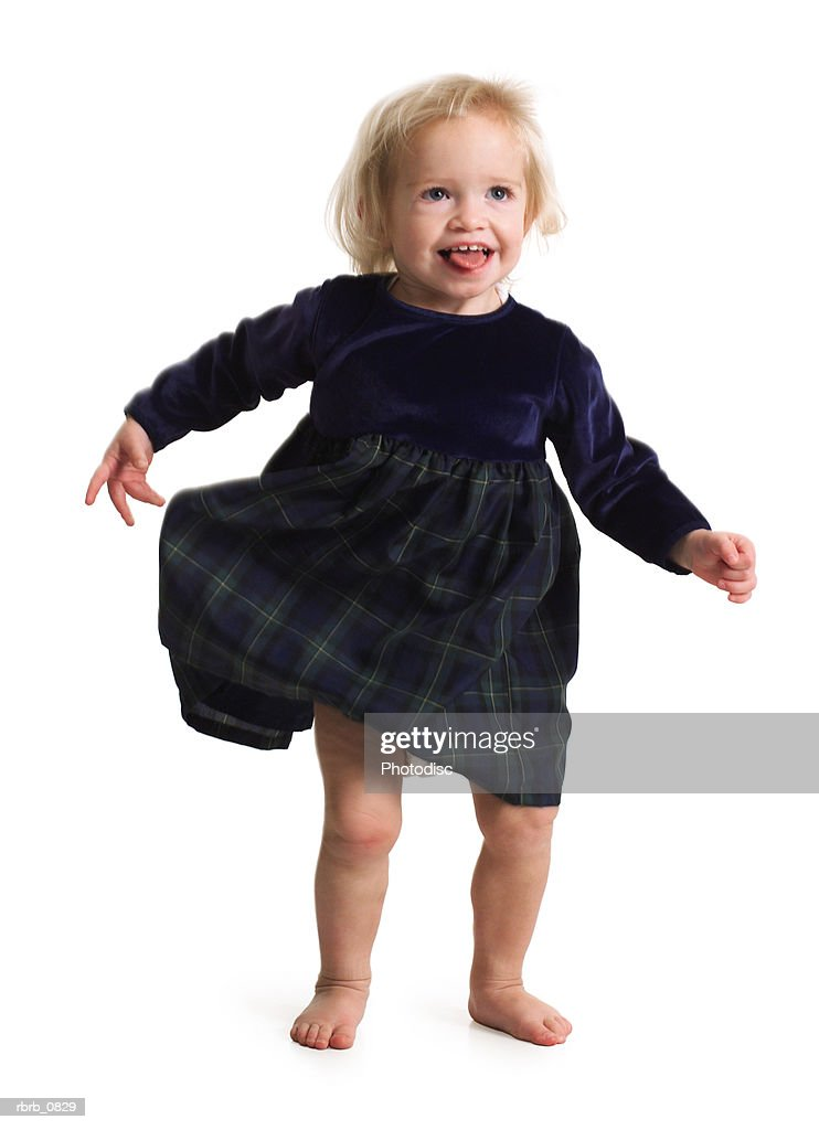 silhouette of a caucasian toddler female child in a black dress as she laughs : Stockfoto