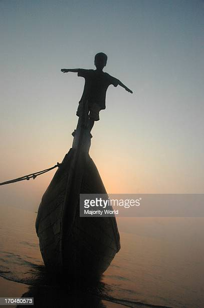 A silhouette of a child on a boat on the shores of the Bay of Bengal in Chittagong Bangladesh February 24 2009