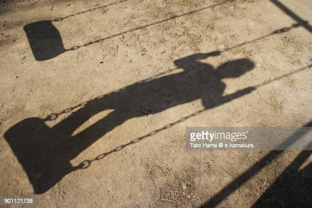 Silhouette of a child sitting on swing in the park in Kamakura city in Kanagawa prefecture in Japan