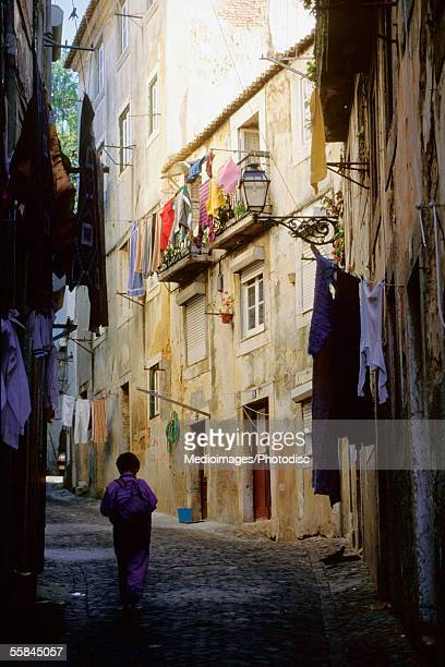 silhouette of a child walking in an alley, alfama quarter, lisbon, portugal - alfama stock photos and pictures
