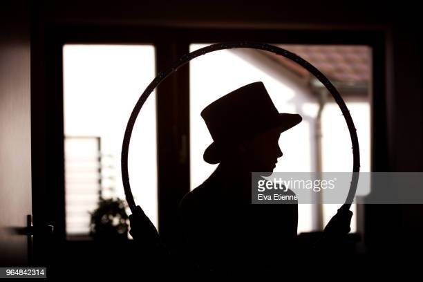 silhouette of a child wearing top hat and holding hoop, standing in a domestic room - magic doors stock pictures, royalty-free photos & images