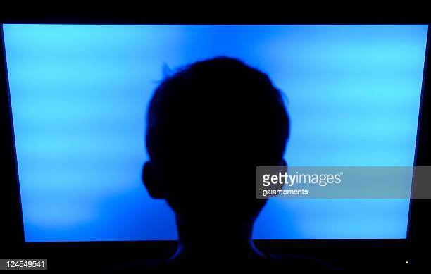Silhouette of a child's head in front of a flat screen TV