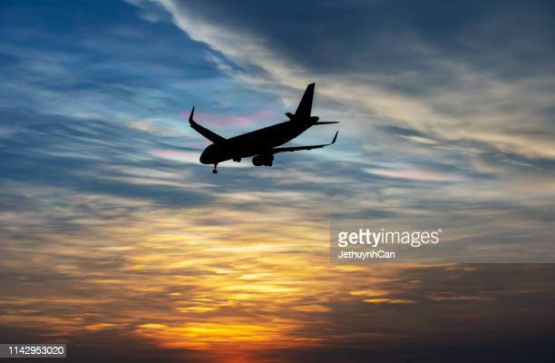 silhouette of a commercial airplane landing against beautiful sunset glow sky - commercial aircraft stock pictures, royalty-free photos & images