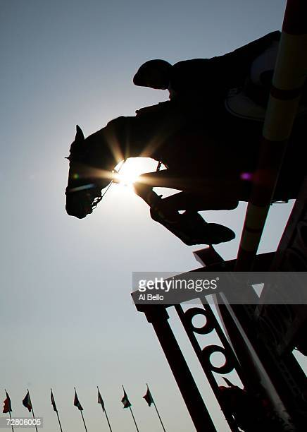 A silhouette of a competitor jumps in the Equestrian Individual Jumping Qualification Round during the 15th Asian Games Doha 2006 at the Doha Racing...