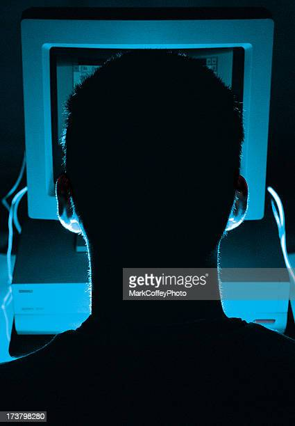 Silhouette of a computer hacker's head from behind screen