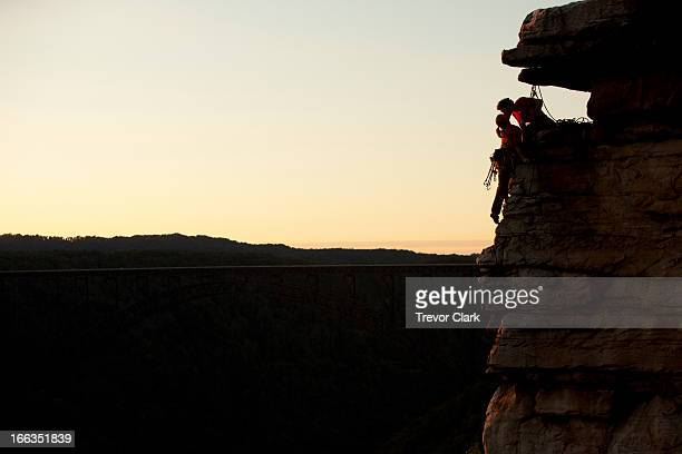 A silhouette of a couple rock climbers kissing on the mountain side.