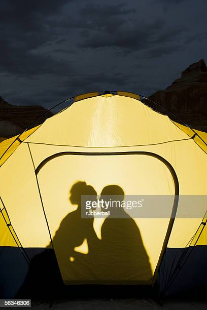 Silhouette of a couple sitting inside a tent