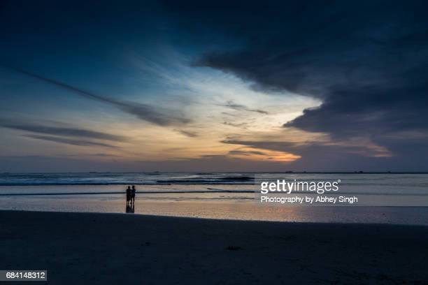 Silhouette of a couple standing on Kochi beach after sunset, Kochi, Kerala, India