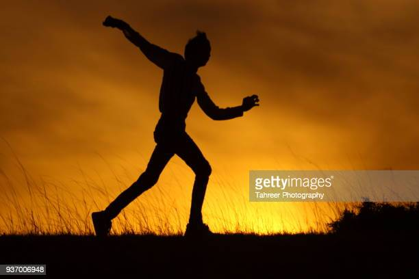 Silhouette of a cricket bowler