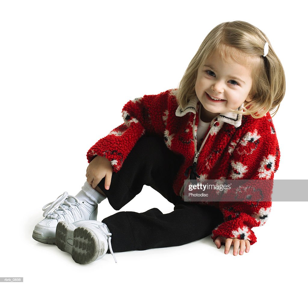 silhouette of a cute caucasian female child in black pants and a red sweater as she sits and smiles : Stockfoto