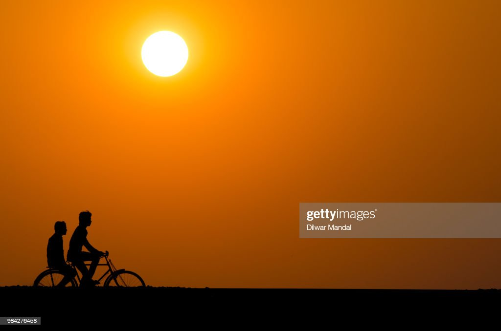 Silhouette of a cyclist men at sunset : Stock Photo