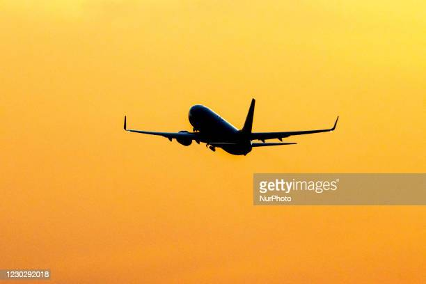 Silhouette of a departing passenger aircraft, a Ryanair low-cost airline Boeing 737-800 during sunset time. The departing airplane of the Irish...