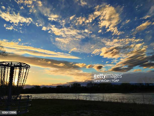 Silhouette of a disc golf at sunset