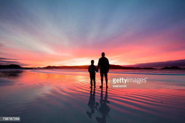 Silhouette of a father and son holding hands on beach at sunset, Western Australia, Australia