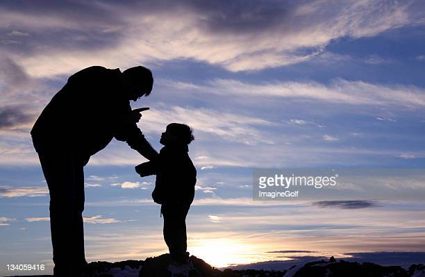 silhouette of a father scolding his child - penalty stock pictures, royalty-free photos & images