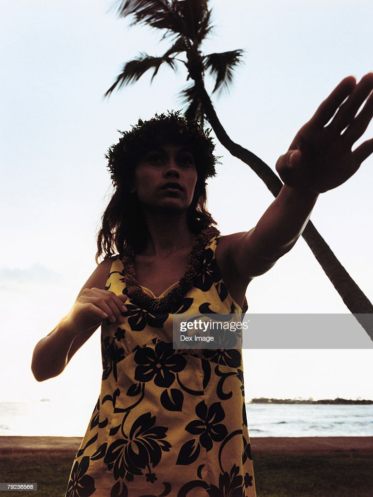 Silhouette of a female hula dancing outdoors at sunset. : Stock Photo