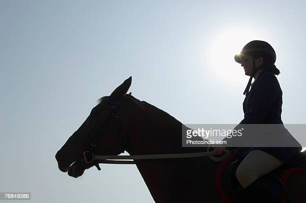Silhouette of a female jockey riding a horse
