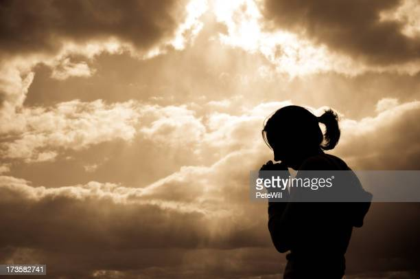 A silhouette of a female praying