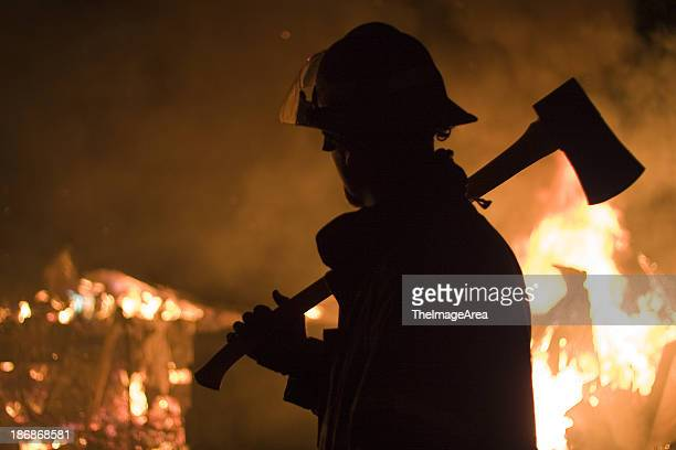 Silhouette of a firefighter with an axe and a fire