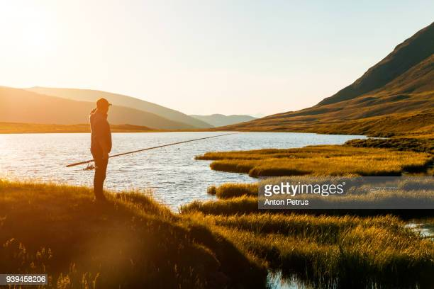 silhouette of a fisherman at sunset on a lake - anton petrus stock pictures, royalty-free photos & images