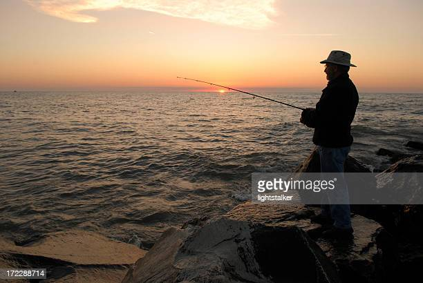 silhouette of a fisherman during sunrise on lake michigan - lake michigan stock pictures, royalty-free photos & images
