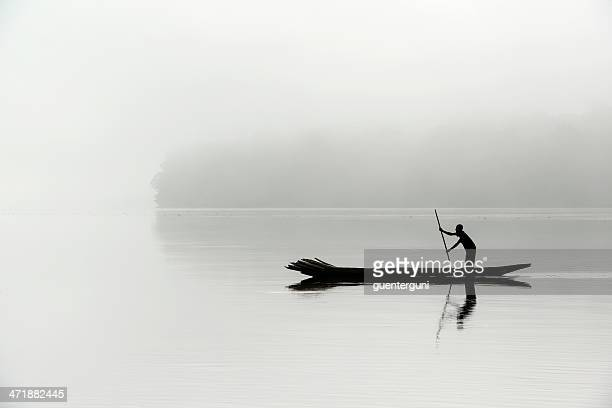silhouette of a fisherman in the morning fog, congo river - dugout canoe stock photos and pictures