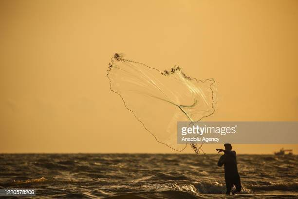 Silhouette of a fisherman is seen as he casts a net to catch fishes in Orontes River at Samandag district in Hatay, Turkey on June 16, 2020.