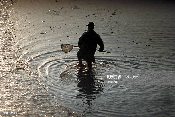 Silhouette of a fisherman standing in the water and holding a fishing net in his hands Austria Around 2004 [Silhouette eines im Wasser stehenden...
