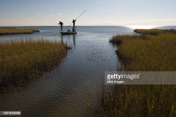 a silhouette of  a fly fisherman and a guide casting for redfish from a flats boat poling skiff in the fresh water marsh south of new orleans, louisiana usa - luisiana fotografías e imágenes de stock