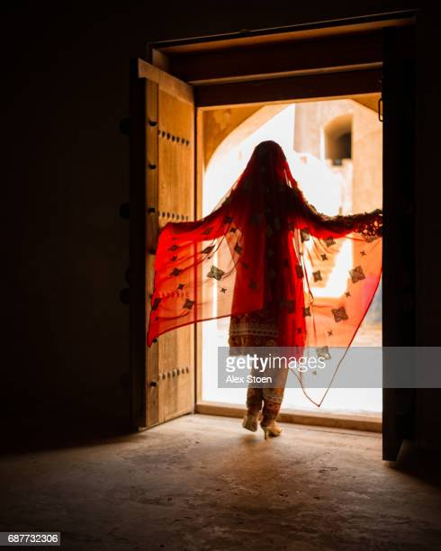 Silhouette of a girl in a red dress standing at the entrance of a old door