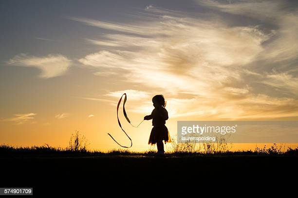 Silhouette of a girl playing with a ribbon
