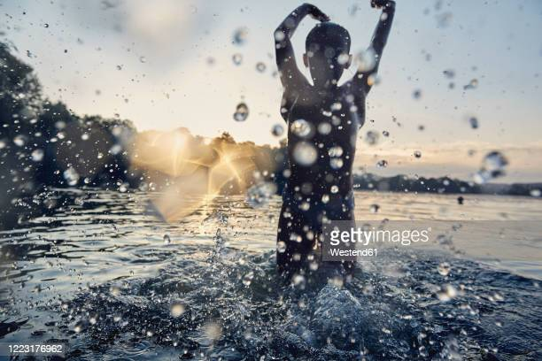 silhouette of a girl splashing in a lake by sunset - high contrast stock pictures, royalty-free photos & images