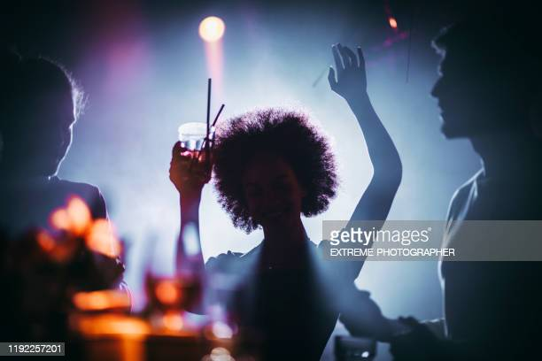 silhouette of a girl with an afro dancing with a cocktail in her hand in a night club - funky stock pictures, royalty-free photos & images