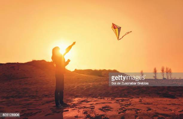 Silhouette of a girl with long hair trailing a kite at sunset