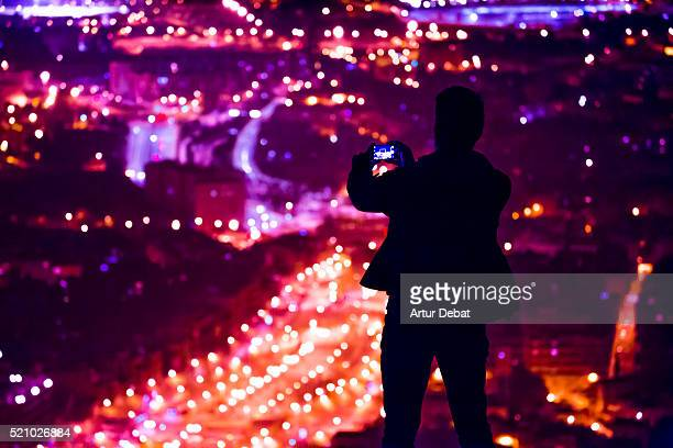 Silhouette of a guy by night contemplating the Barcelona city from the bunkers hill viewpoint taking pictures with smartphone of the bokeh city lights.