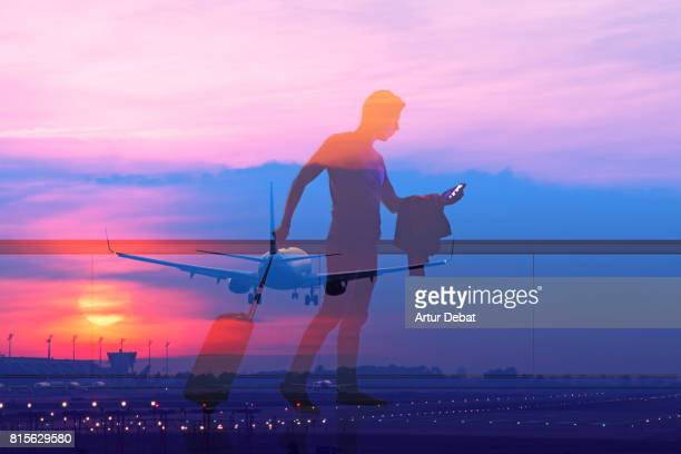 Silhouette of a guy checking his smartphone ready to departure on a airport at sunset with double exposure effect during a travel with trolley suitcase using application technology to get information about the trip.