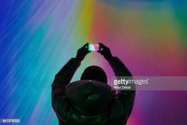 Silhouette of a guy taking pictures with smartphone and the beautiful colorful northern lights falling from the sky in Iceland in a stunning clear and nice lights with the sky full of stars. Aurora borealis.