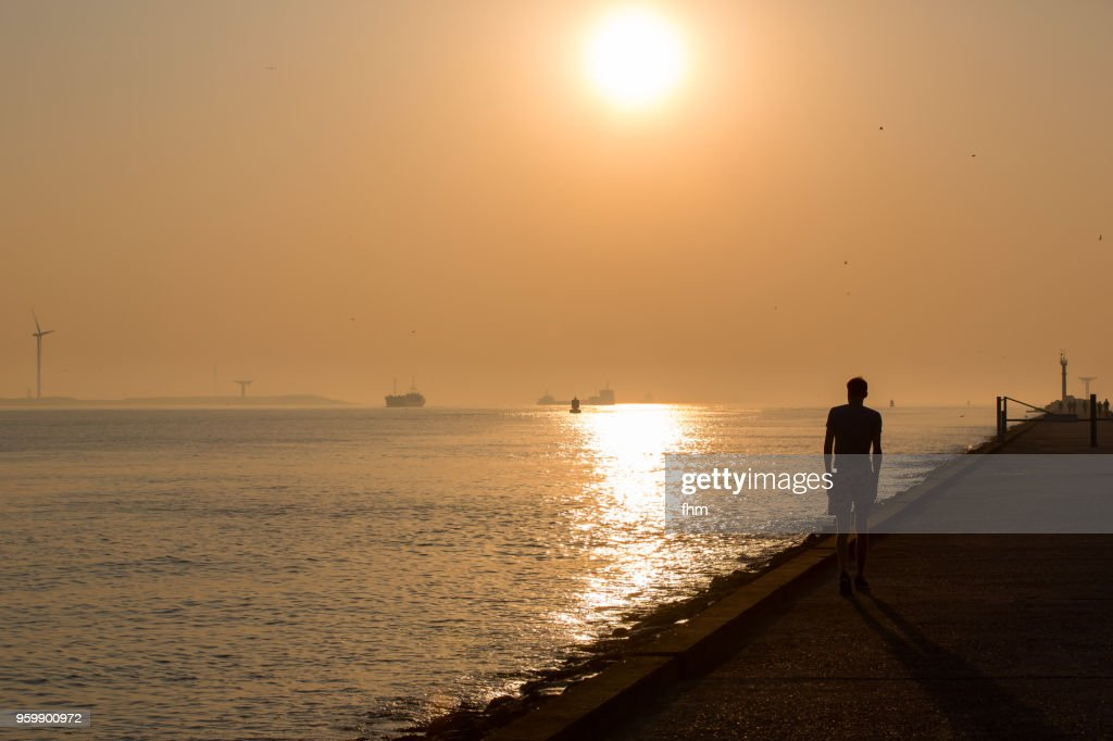 Silhouette of a guy walking on the mole near the sea at sunset (Rotterdam/ Hook of Holland, Netherlands) : Stock-Foto