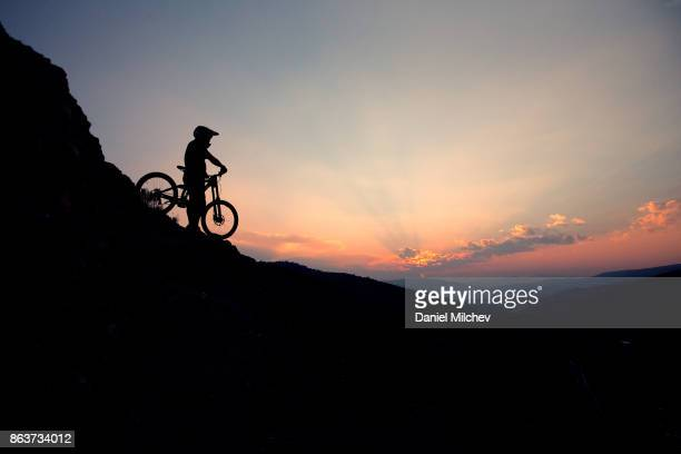 silhouette of a guy with mountain bike wearing  helmet against the sky at sunset. - avon colorado stock photos and pictures