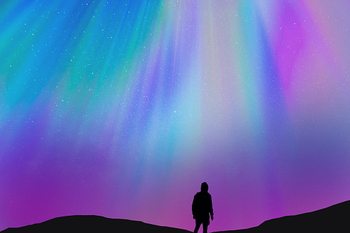 Silhouette of a guy with the beautiful colorful northern lights falling from the sky in Iceland in a stunning clear and nice lights with the sky full of stars. Aurora borealis. - gettyimageskorea