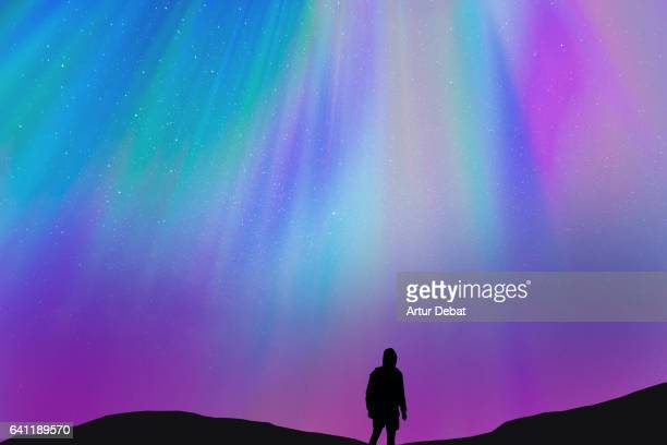 silhouette of a guy with the beautiful colorful northern lights falling from the sky in iceland in a stunning clear and nice lights with the sky full of stars. aurora borealis. - ethereal stock pictures, royalty-free photos & images